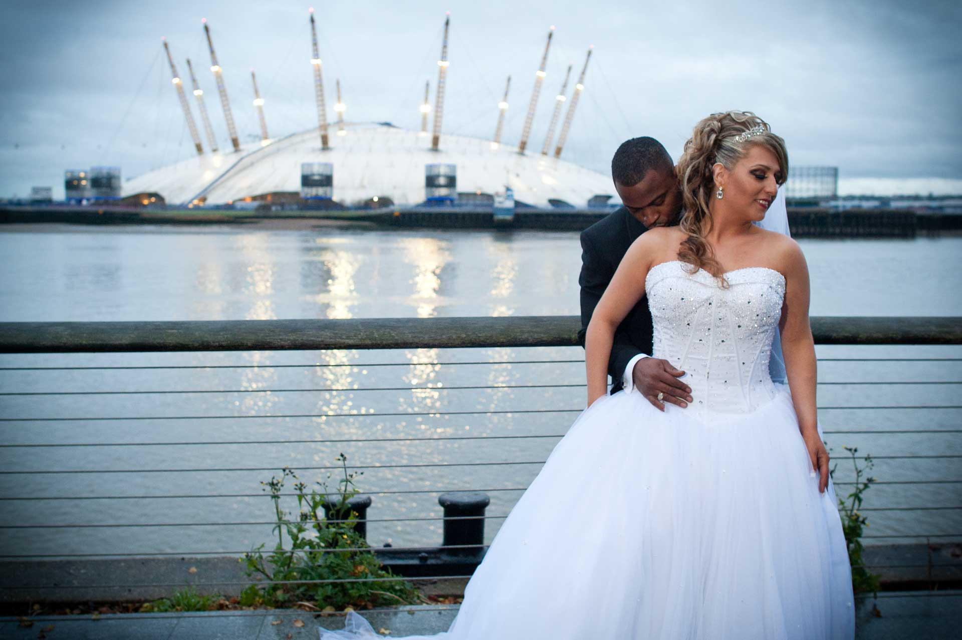 Groom Kisses his bride in front of london millenuium dome